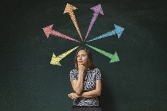 Woman standing in front of chalk board thinking