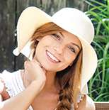Lady with sunhat tilting her head smiling