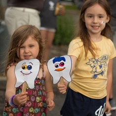 Two young girls smiling at community event