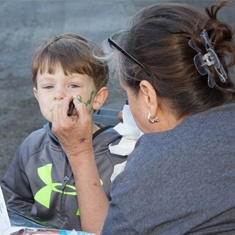 Child having face painted at community event