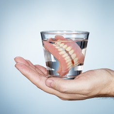 Dentures soaking in a glass of water