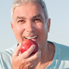Man with dental implants biting into an apple.