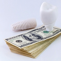Dental implant on a stack of money.