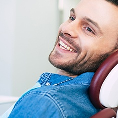 Man in dental chair smiling after dental implant tooth replacement