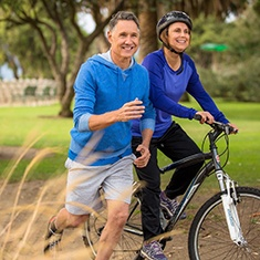 Older couple running and biking together after dental implant tooth replacement