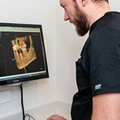 A dental professional reviewing the images captured of a patient's oral and facial structure to plan their dental implant placement