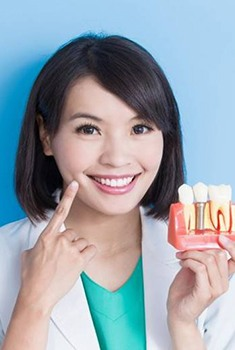 Smiling dentist holding model of dental implants in Arlington Heights