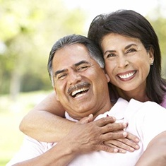 Smiling couple with dental implants in Arlington Heights