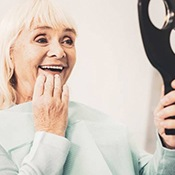 Smiling woman admires her new dental implants in Arlington Heights