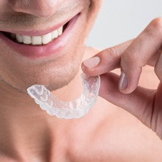 A man holding an Invisalign aligner