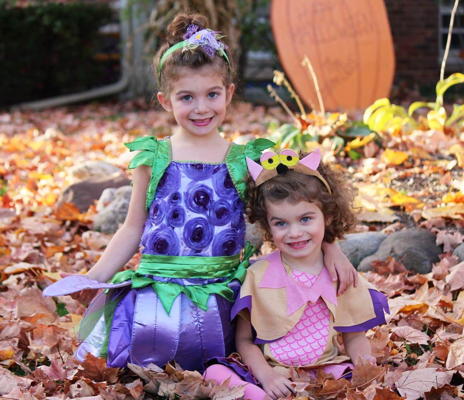 Two girls in costumes playing in leaves