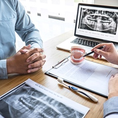 dentist explaining dental implant supported denture X-rays to a patient