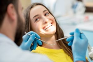 Smiling woman getting a root canal from her Arlington Heights dentist