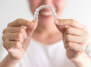 Smiling woman holds out set of Invisalign in Arlington Heights