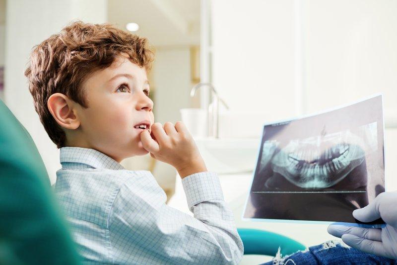 dentist showing child their dental x-ray